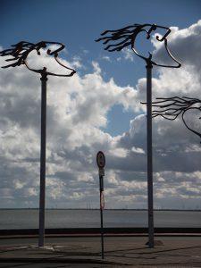 """Die """"WINDWÄCHTER"""", drei Stahlplastiken des Dipl. Designers Klaus Evenburg prägen seit dem 9. Juli 2000 das Bild des Wilhelmshavener Fliegerdeiches am Südstrand in Wilhelmshaven. Die sieben bis neun Meter hohe Skulpturengruppe symbolisiert stellvertretend die Nähe des Menschen zu den Naturgewalten von Wind und Meer, und die Auseinandersetzung mit Ihnen. Sie stehen für den Bewohner der Küste, der ständig die Nähe der Naturgewalten sucht."""