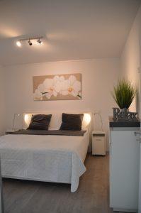 Belegungsplan des Ferienhauses Aldenburg, das Schlafzimmer ist mit einem Boxspringbett, einer Kommode mit Schubläden, zwei Nachttischen sowie einem Kleiderschrank mit Schiebetüren ausgestattet.